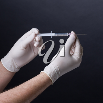 Male hands in latex gloves holding a syringe on dark background