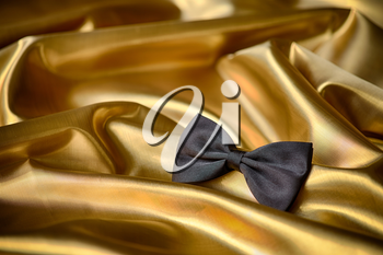 Black bow tie on draped golden satin