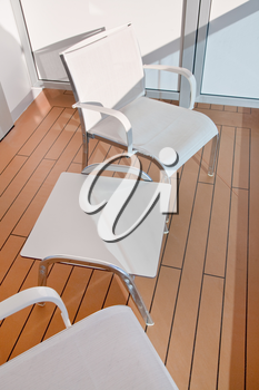 two textile chairs and table on balcony of cruise liner