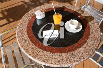 fresh orange juice and cappuccino on no smoking table in outdoor cafe on cruise liner
