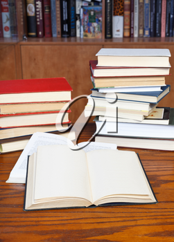 two open books on wooden table near bookcases