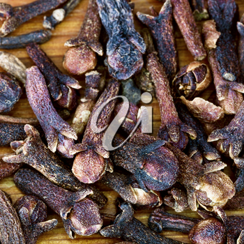 macro view of dried cloves on wooden board