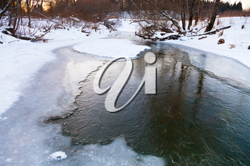 frozen riverbank of forest stream at winter sunset