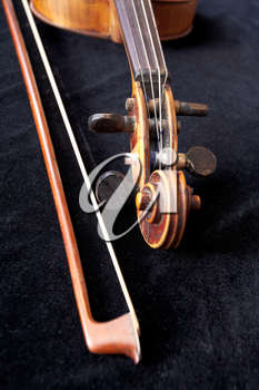 fiddle scroll and bow on black velvet close up