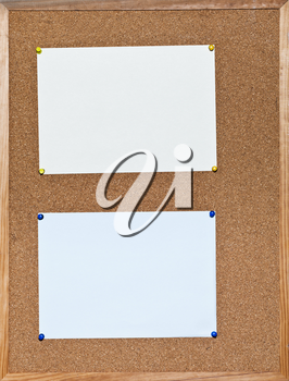 blue and yellow sheets of paper on cork board in wooden frame
