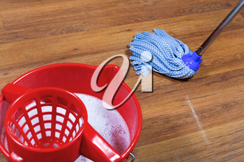 red bucket with water and mopping of parquet floors
