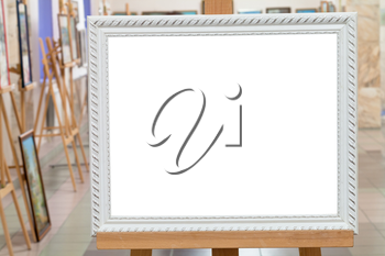 white picture frame with white cut out canvas on easel in art gallery hall