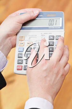 above view of calculator in male hands close up