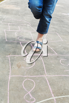 girl hops in hopscotch outdoors in sunny day