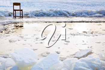 icebound chair near ice hole in frozen lake in cold winter day