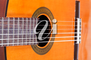 body of spanish acoustic guitar with six nylon strings close up