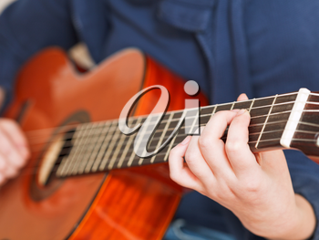 woman plays on classical acoustic guitar close up