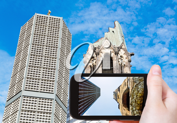 travel concept - tourist taking photo of gedachtniskirche church on mobile gadget in Berlin, Germany