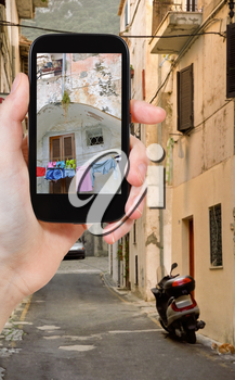 travel concept - tourist taking photo of small side street in italian town San Felice Circeo on mobile gadget, Italy