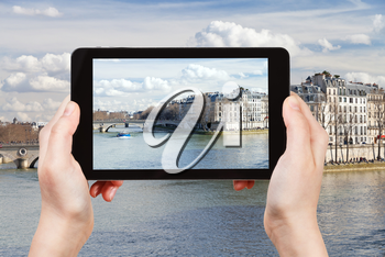 travel concept - tourist taking photo of Seine river and Pont Louis-Philippe in Paris on mobile gadget, France