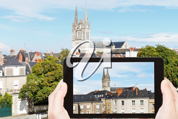 travel concept - tourist takes picture of urban houses and Saint Maurice Cathedral in Angers, France on smartphone,