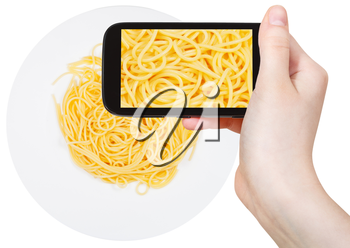photographing food concept - tourist takes picture of italian spaghetti al burro on plate on smartphone, Italy