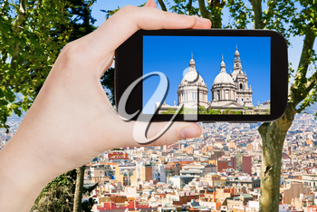 travel concept - tourist takes picture of National Art Museum of Catalonia and Barcelona skyline on smartphone, Spain