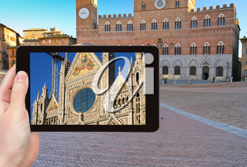 travel concept - tourist takes picture of Cathedral of Siena and Piazza del Campo - Europe's greatest medieval squares, Siena, Italy, on tablet pc