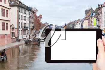 travel concept - tourist photograph bridge on Ill river canal in old Strasbourg town, France on tablet pc with cut out screen with blank place for advertising logo