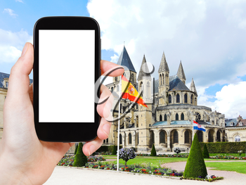 travel concept - tourist photograph medieval Abbey of Saint-Etienne (Abbaye aux Hommes) in Caen city, France on smartphone with cut out screen with blank place for advertising logo