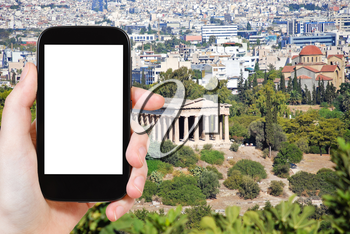 travel concept - tourist photograph Temple of Hephaestus and Athens city view from Acropolis hill, Greece on smartphone with cut out screen with blank place for advertising logo