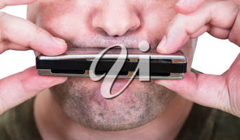 unshaven street musician playing harmonica close up
