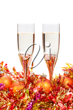 two glasses of champagne at golden and orange Christmas baubles isolated on white background