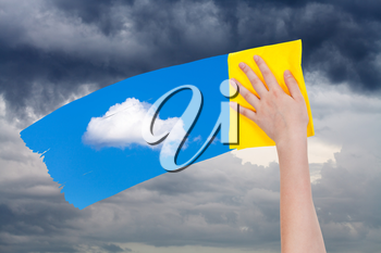 weather concept - hand deletes rain clouds by yellow cloth from image and blue sky with white cloud is appearing