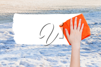 season concept - hand deletes winter snow by orange rag from image and white empty copy space are appearing