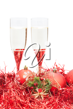 two glasses of sparkling wine and angel figure at red Christmas decorations isolated on white background