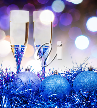 Christmas still life - two glasses of sparkling wine at blue Xmas decorations with violet blurred Christmas lights bokeh background
