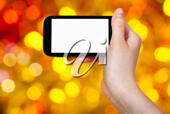 christmas party concept - hand with smartphone with cut out screen on background from brown, yellow and red twinkling Christmas lights bokeh of electric garlands on Xmas tree