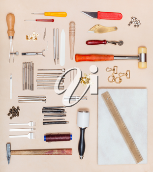 top view of various leatherwork tools and marble board on natural leather surface