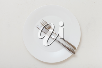 food concept - top view of white plate with parallel knife, spoon on white plastering board