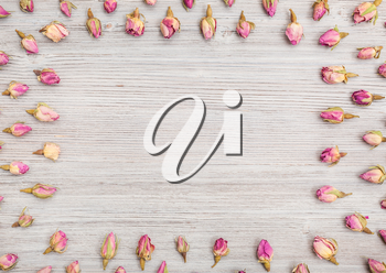 frame from natural pink rose flower buds on wooden table