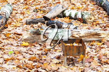 forgotten small barbecue grill with trash on meadow covered by fallen leaves in city park in autumn