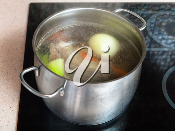 cooking soup - simmering meat broth in stockpot on ceramic cooker