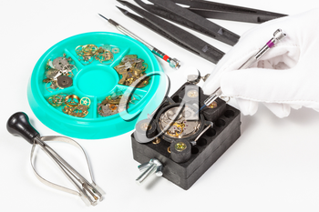watchmaker workshop - repair of old mechanic wristwatch on white table
