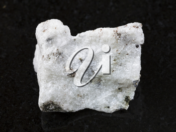 macro shooting of natural mineral rock specimen - raw carbonatite stone on dark granite background