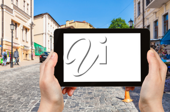 travel concept - tourist photographs Andriyivskyy Descent street in Podil district of Kiev city in Ukraine on tablet with cut out screen for advertising logo