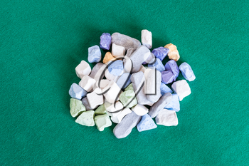 top view of pile of various multicolored stones on green baize table