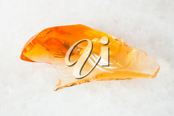 macro shooting of natural mineral - crystal of fire opal gem on white marble from Ural Mountains