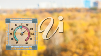 outdoor thermometer on home window and blurred yellow urban garden on background in sunny warm autumn day