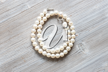 folded natural white pearl necklace on gray wooden board