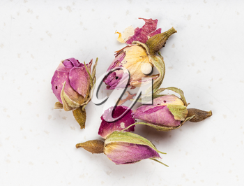 several old dried rosebuds close up on gray ceramic plate