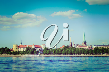 Vintage retro hipster style travel image of View of Riga over Daugava river: Riga Castle, St. James's Cathedral, St. Peter's Church. Riga, Latvia