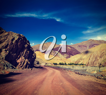 Vintage retro effect filtered hipster style travel image of Travel forward concept background - road Himalayas with mountains. Manali-Leh road, Ladakh, Jammu and Kashmir, India
