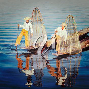 Vintage retro effect filtered hipster style image of Myanmar travel attraction. Traditional Burmese fisherman with fishing net at Inle lake famous for their distinctive one legged rowing style