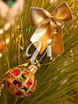 Christmas bow and ball on a green pine branch.